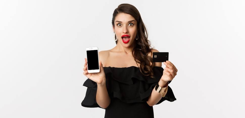 zszokowana kobieta w pięknej sukni trzyma telefon i kartę bankową używając technologii do zakupów modowych