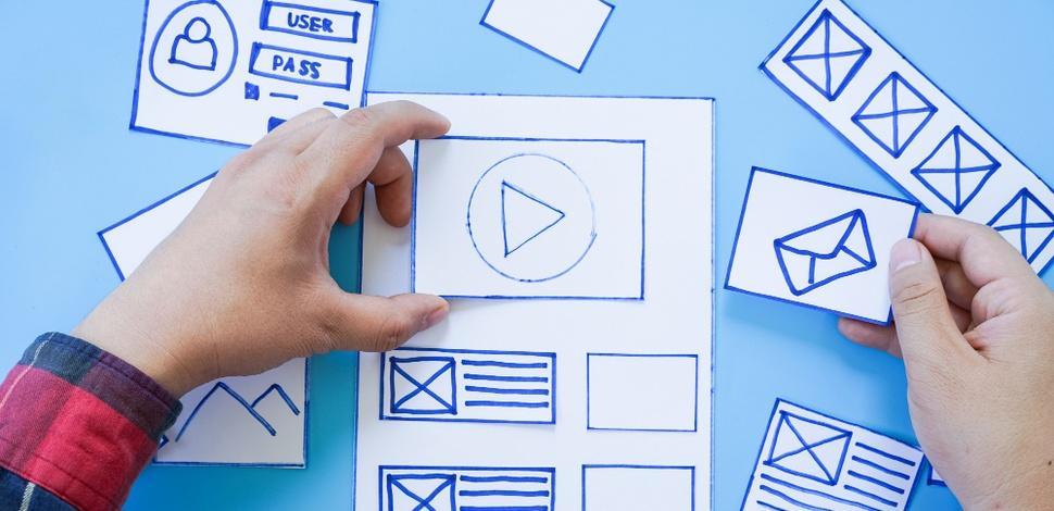 osoba projektująca UX za pomocąwyciętych na kartce elementów strony internetowej