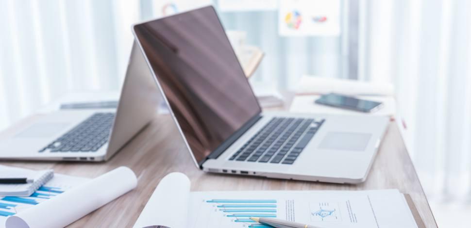 Rozłożone laptopy i notatki danych w miejscu pracy.
