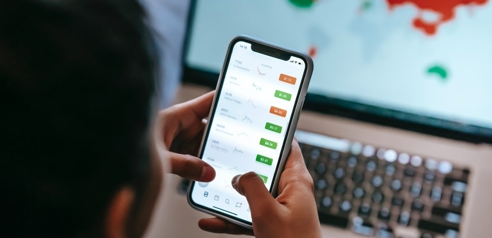 Osoba sprawdzająca dane na smartfonie przy biurku w biurze.