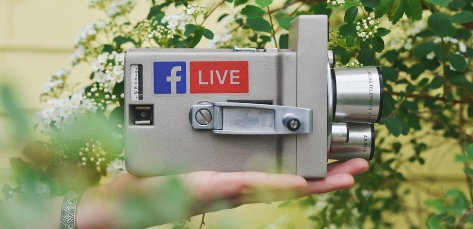 ręka podtrzymująca kamerę z przylepkami facebook i live.