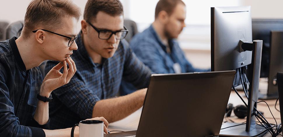 dwaj-pracownicy-w-biurze-przed-laptopem