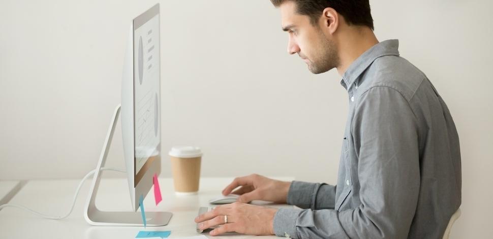 skupiony mężczyzna pracuje przy komputerze