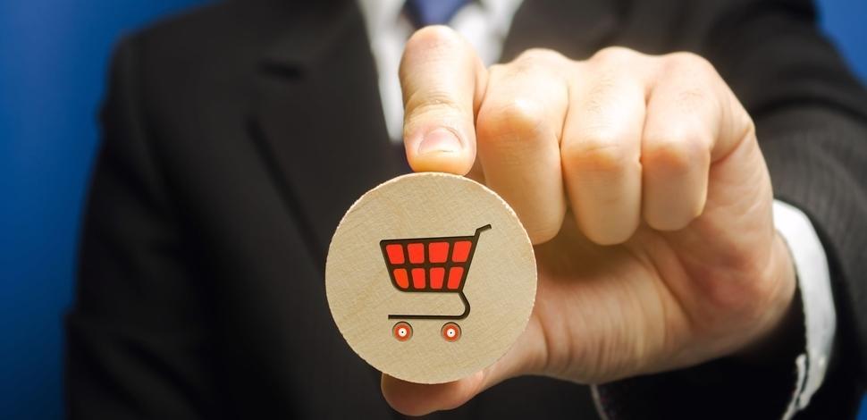 mężczyzna trzymający drewniany blok ze znaczkiem wózka zakupowego