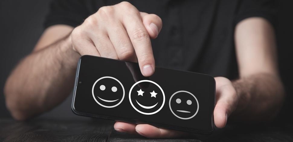 mężczyzna wskazujący palcem na emotikony oznaczające ocenę satysfakcji klienta