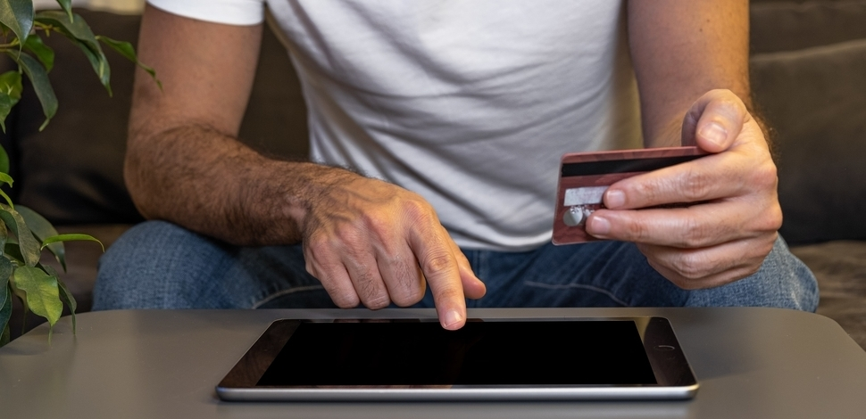 mężczyzna trzymający kartę kredytową i płacący za zakupy na tablecie