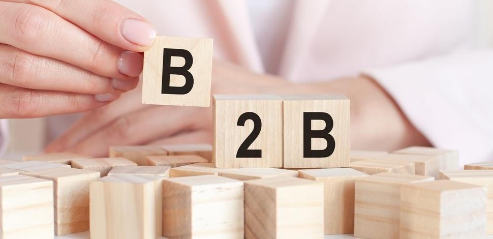ręka układające drewniane klocki w napis B2B