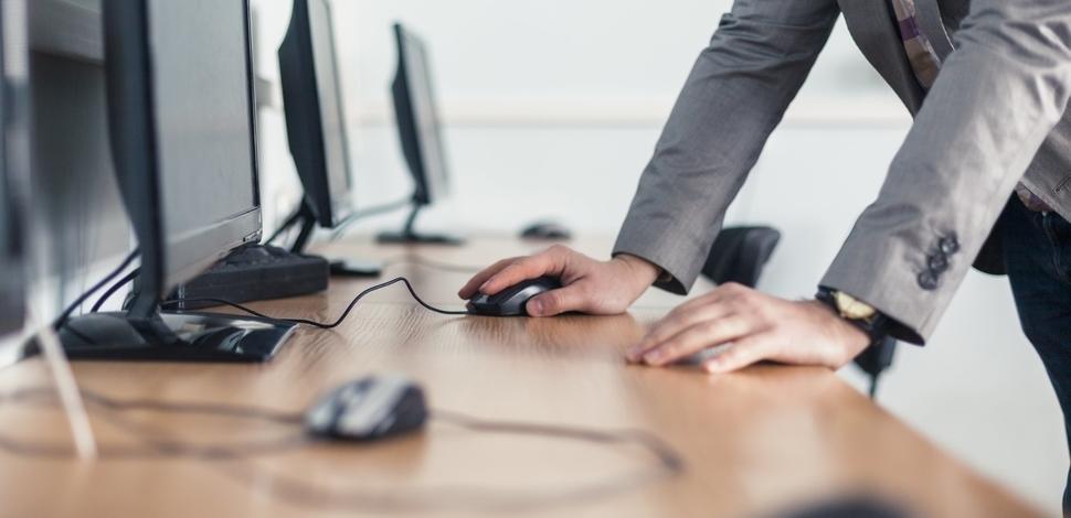 zbliżenie na ręce mężczyzny opierające się na biurku przy komputerze