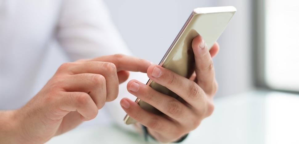 mężczyzna przesuwający palcem po ekranie smartfona