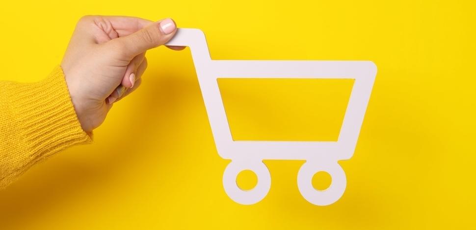dłoń trzymająca wózek zakupowy z papieru na żółtym tle