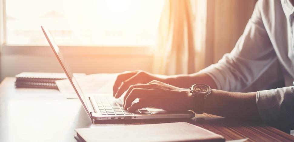 zbliżenie na dłonie piszące na laptopie w tle zachodzącego słońca