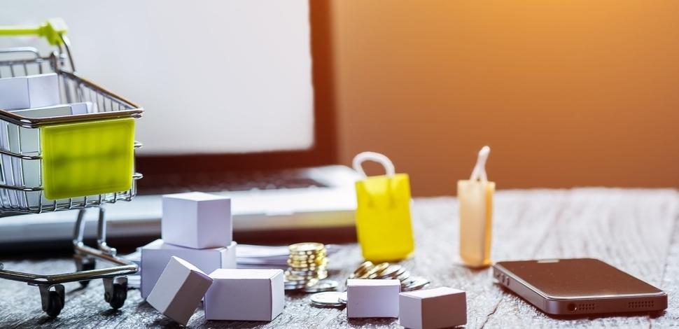 makieta wózka zakupowego, monety i małe torby rozrzucone na biurku
