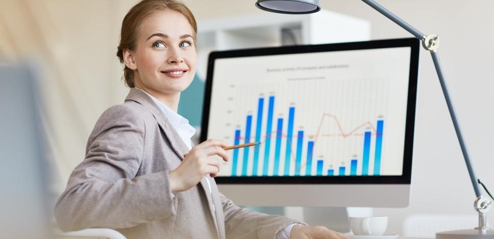 kobieta siedząca przy komputerze na którym jest wykres