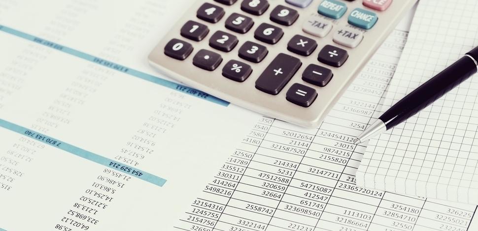 leżąca kartka z liczbami, a na niej długopis i kalkulator