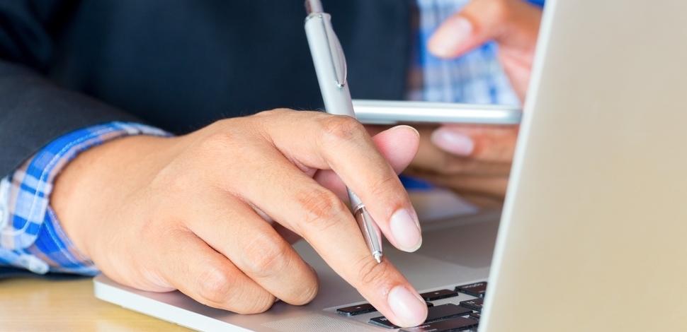 osoba pisząca na laptopie jednocześnie trzymająca długopis i telefon