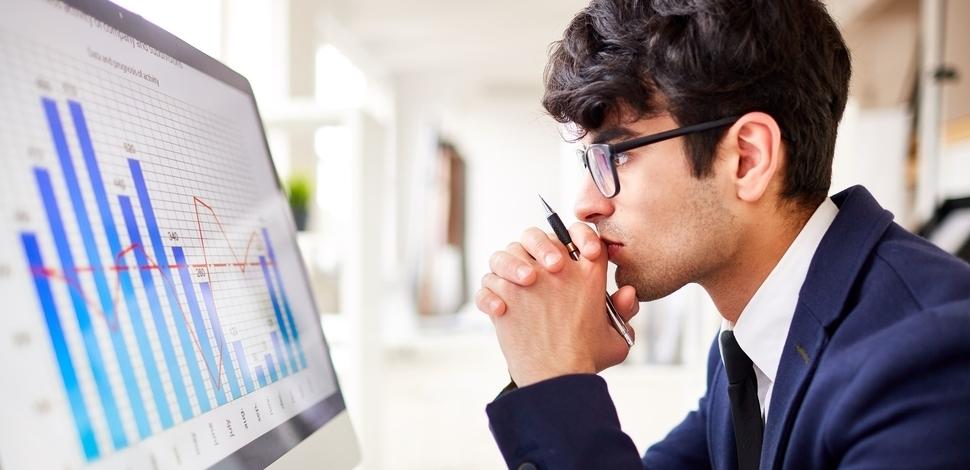 skupiony mężczyzna siedzący przed komputerem analizujący wykresy