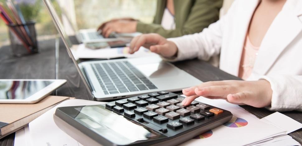 kobieta jednocześnie używająca kalkulatora i pisząca na laptopie w biurze