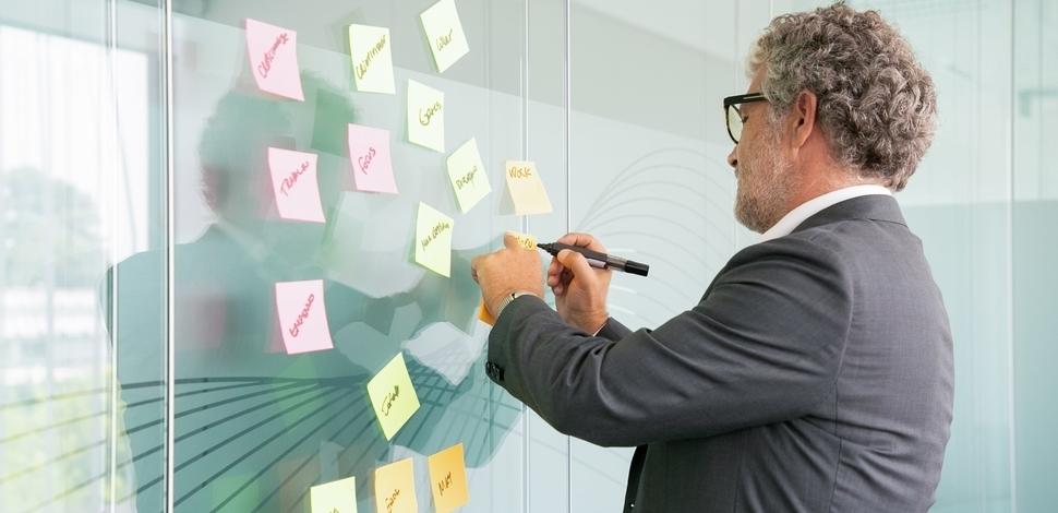 skoncentrowany biznesmen piszący markerem po kolorowych karteczkach
