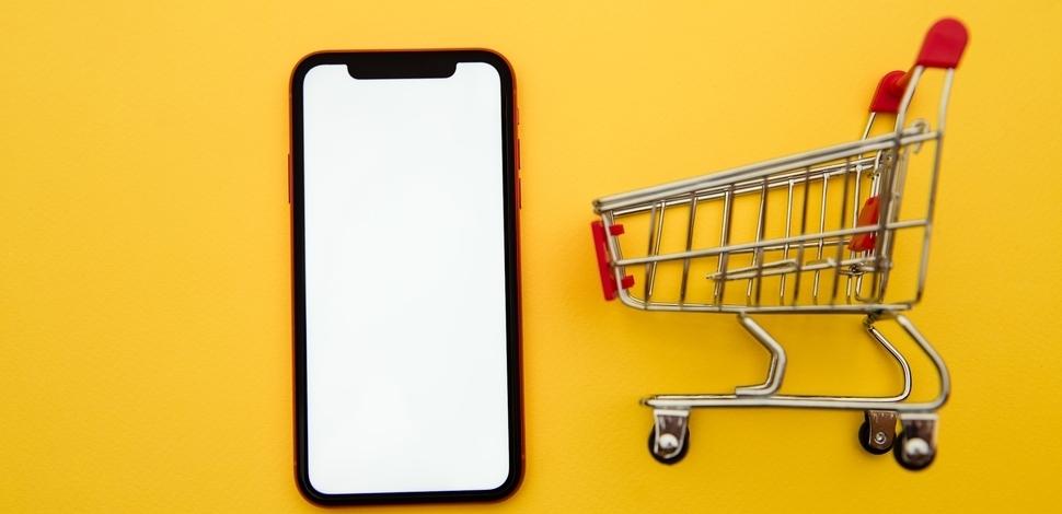 makieta wózka zakupowego oraz telefon komórkowy na żółtym tle