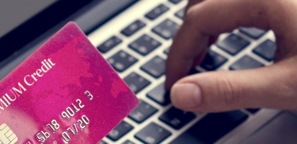 karta płatnicza i osoba pisząca na klawiaturze laptopa