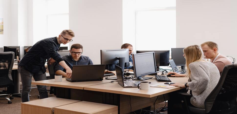 grupa młodych ludzi w pracy siedząca przy komputerach