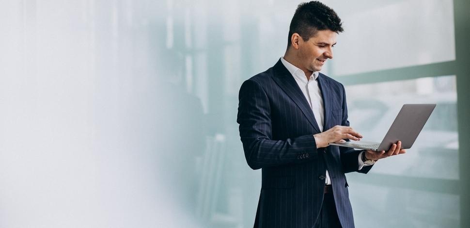 młody biznesmen trzymający laptopa w rękach