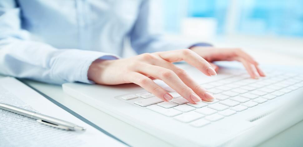 człowiek piszący tekst na klawiaturze