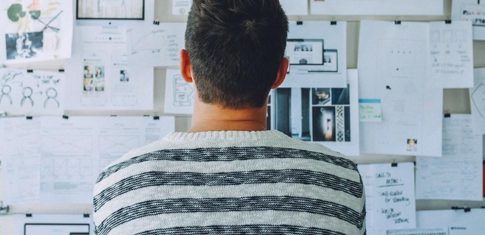 Osoba patrząca na tablicę korkową z notatkami i tabelkami.