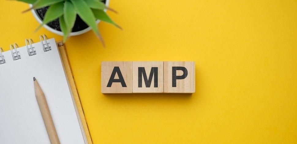 kostki na żółtym biurku z napisem amp skrót od accelerated mobile pages