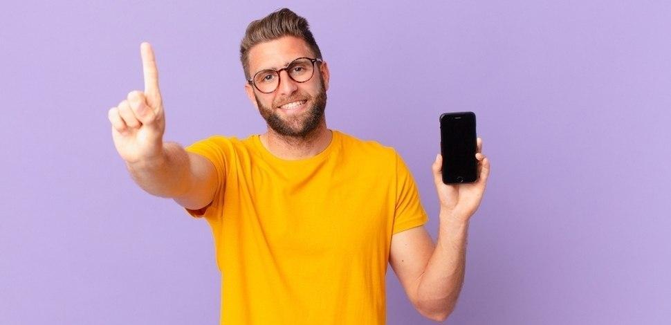 mężczyzna z telefonem w ręku podnoszący rękę - metafora mobile first