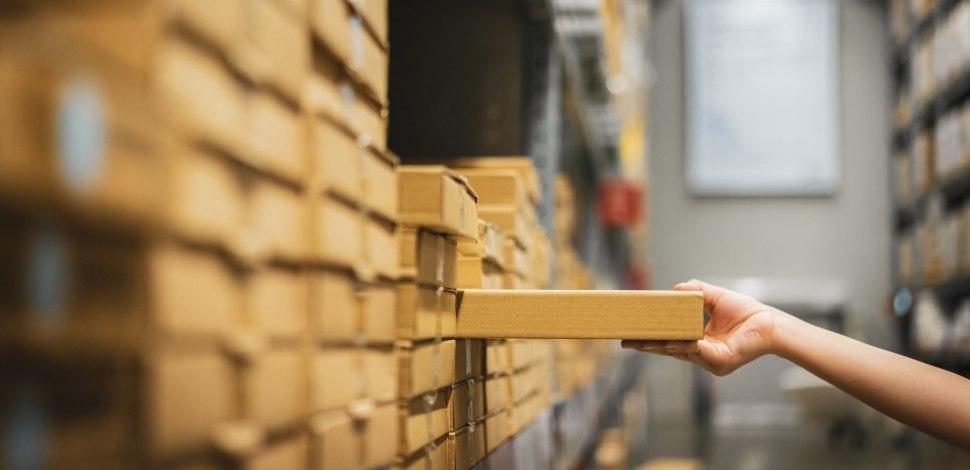 pracownik wyciąga produkt z półki w magazynie sklepu